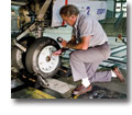 Photo of an aircraft technician checking the tire pressure of the nose gear on a Boeing 737