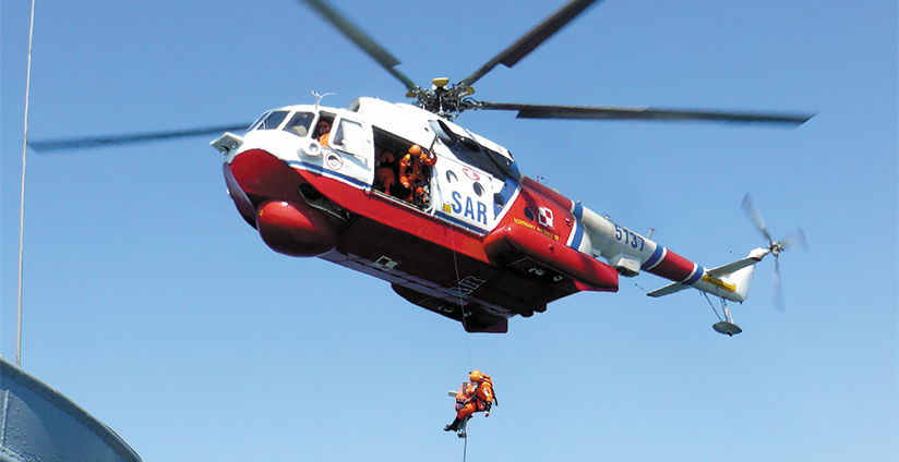 SAR helicopter rescuing man.